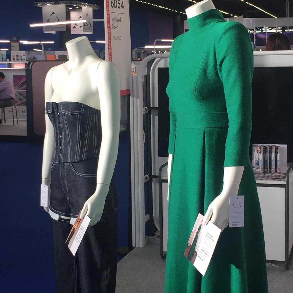 Kaksi mallinukkea, joilla päällä farkkuasu ja vihreä mekko.
