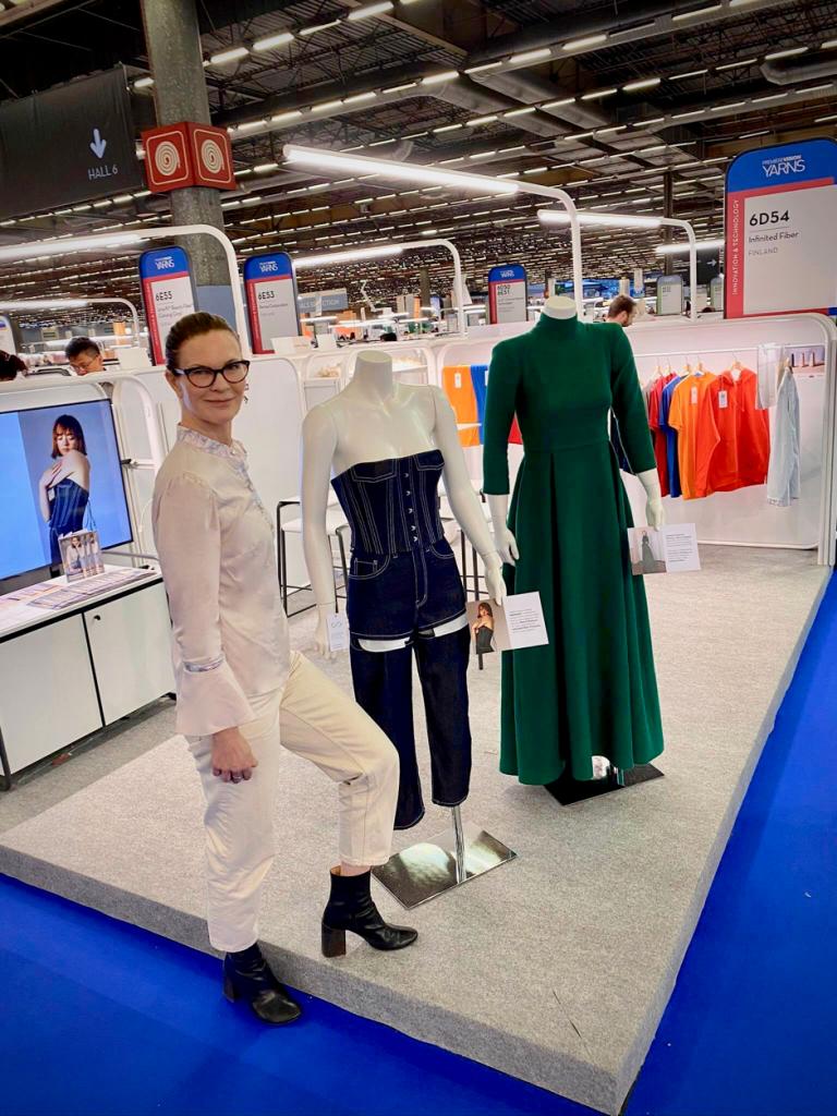 Nainen seisoo kahden mallinuken vieressä. Nukkeilla on sininen haalari ja vihreä mekko.