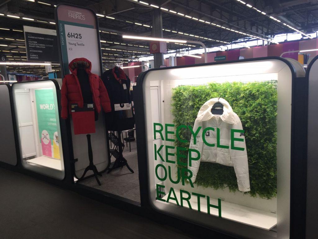 """Näyteikkunassa valkoinen takki, lasissa teksti """"recycle keep our earth"""""""