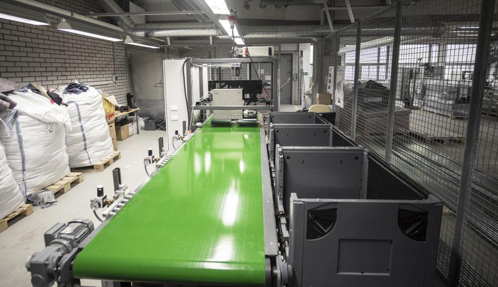 REISKAtex®-laitteisto loppupäästä katsottuna. Hihnakuljettimen alussa näkyvä harmaa laatikko on NIR-analysaattori. Vasemmassa laidassa ovat paineilmapuhaltimet, ja oikeassa laidassa ovat kuitukohtaiset laatikot tunnistetuille tekstiilijakeille