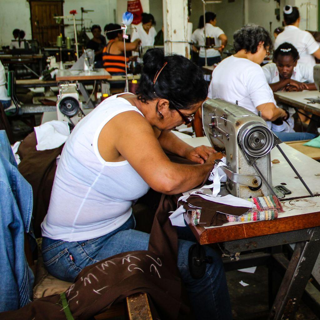 Nainen ompelemassa vaatteita tehtaalla