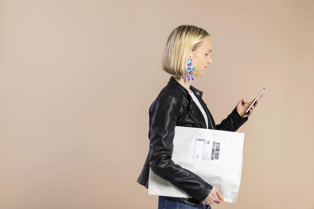 Nainen kantaa postpakettia